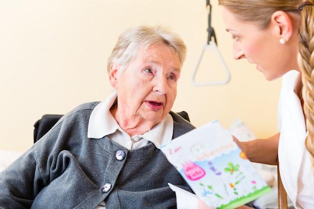 Infirmière donnant une carte d'anniversaire à une femme âgée à la maison Photo Premium