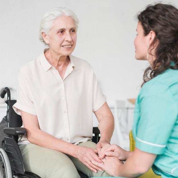 Infirmière handicapée heureuse assis sur une chaise roulante en regardant concierge Photo gratuit