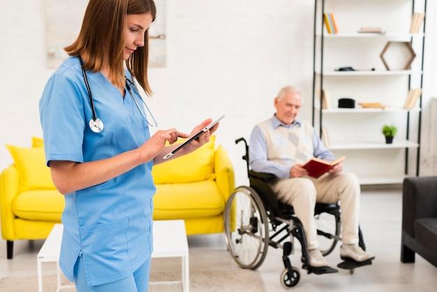 Infirmière Moyen Vérifiant Sa Tablette Photo gratuit