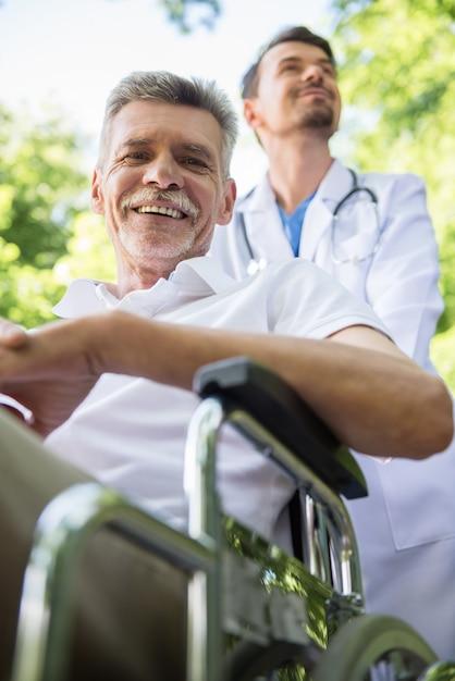 Infirmière à pied avec patient senior en fauteuil roulant dans le jardin. Photo Premium