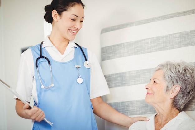 Infirmière prenant soin d'une femme âgée malade dans la chambre Photo Premium