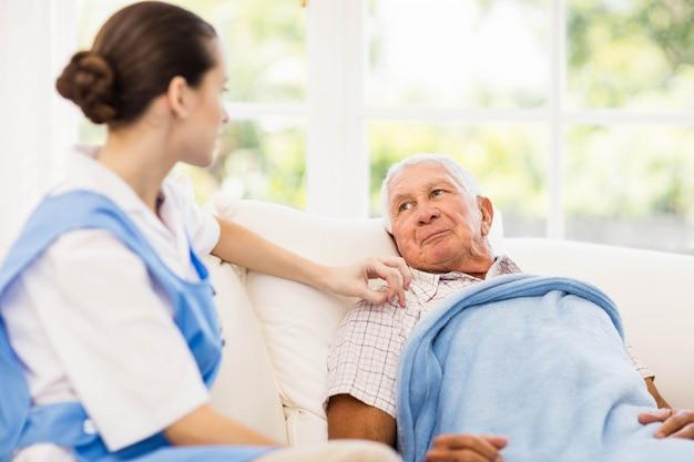 Infirmière prenant soin d'un patient âgé malade à la maison Photo Premium