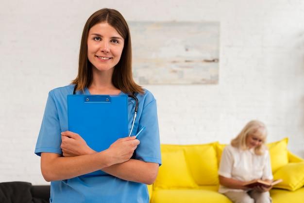 Infirmière Avec Le Presse-papier Bleu En Regardant La Caméra Photo gratuit