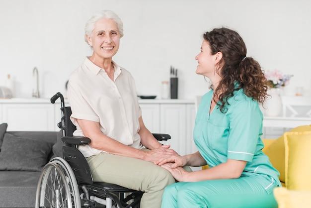 Infirmière en regardant un patient handicapé assis sur une chaise roulante Photo gratuit