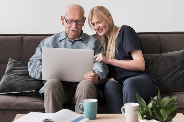 Infirmière Smiley Montrant Le Vieil Homme L'ordinateur Portable Photo gratuit