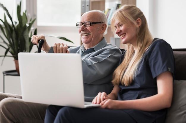 Infirmière Smiley Et Vieil Homme Utilisant Un Ordinateur Portable Photo Premium