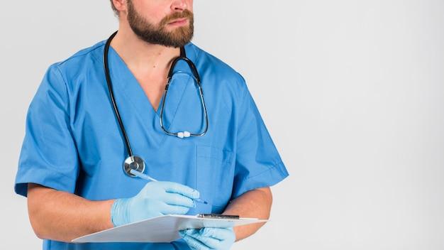 Infirmière tenant et écrivant dans le presse-papiers Photo gratuit