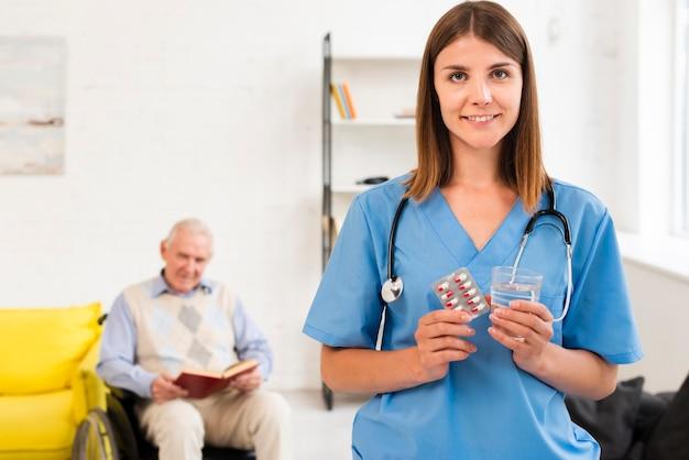 Infirmière tenant des pilules et un verre d'eau Photo gratuit