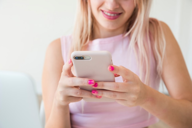 Influence Blonde Utilisant Un Téléphone Mobile Photo gratuit