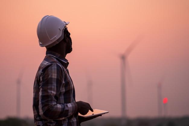 Ingénieur africain portant un casque blanc debout avec tablette numérique contre les éoliennes par journée ensoleillée Photo Premium