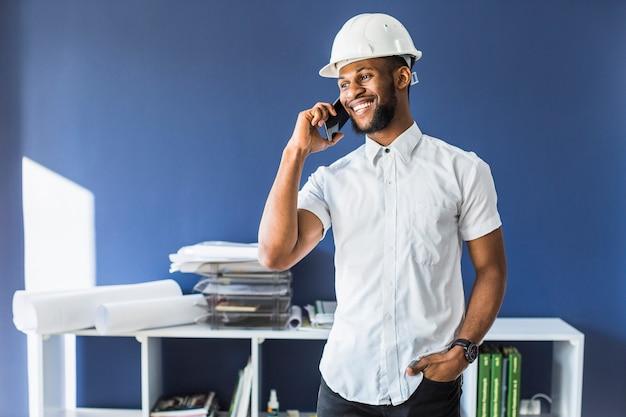 Ingénieur afro-américain heureux, parler au téléphone mobile dans le bureau Photo gratuit