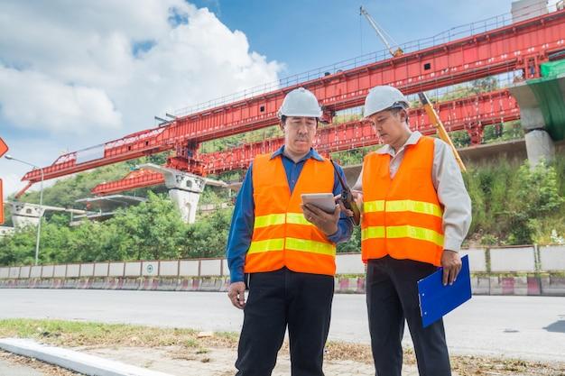 Un ingénieur ou un architecte consulte sur une tablette numérique pour superviser ou gérer un projet autoroutier ou autoroutier Photo Premium