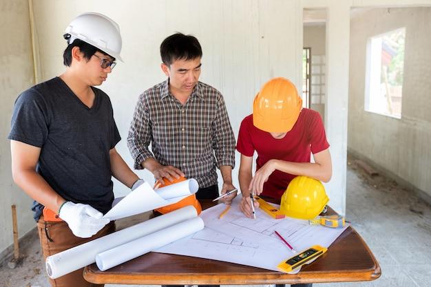 Ingénieur et architecte discutant avec le contremaître sur un chantier de construction Photo Premium
