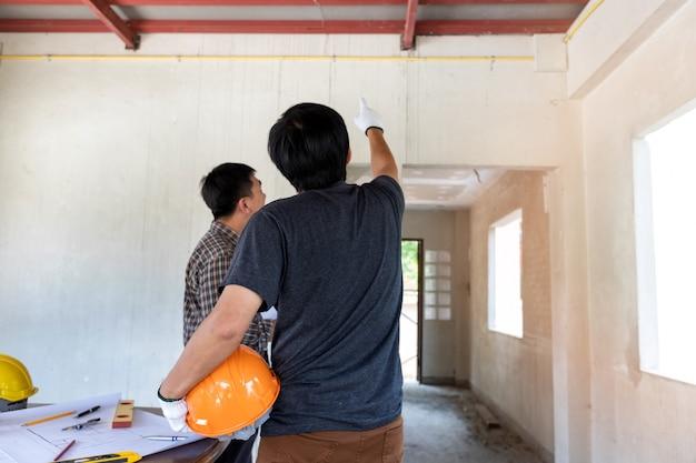 Ingénieur ou architecte discutant avec un contremaître sur un chantier de construction Photo Premium