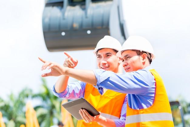 Ingénieur asiatique discutant des plans sur un chantier de construction Photo Premium