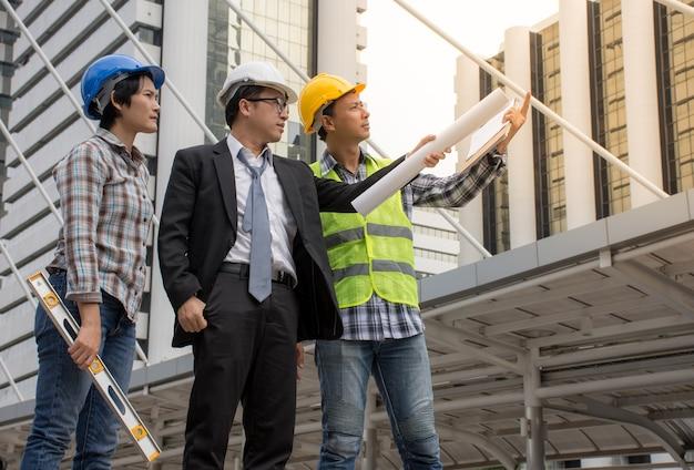 Ingénieur asiatique et équipe d'architectes vérifiant la construction sur le chantier Photo Premium