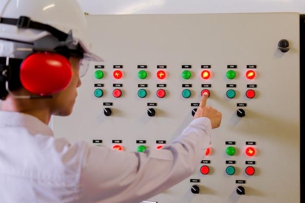 L'ingénieur est en train de vérifier le panneau de commande électrique en usine / le panneau de commande système prêt. Photo Premium