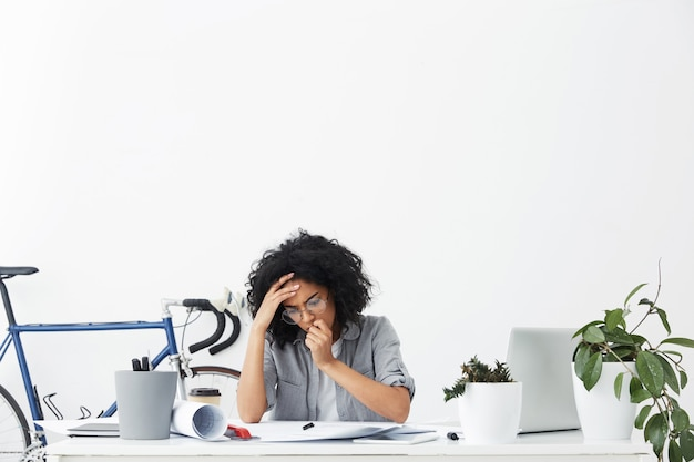 Ingénieur Femme Frustrée Vérifiant Ses Dessins Techniques Photo gratuit