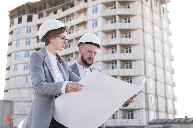 Ingénieur homme et femme tenant un plan alors qu'il travaillait sur un chantier de construction Photo gratuit