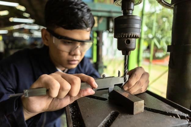 Un ingénieur industriel, coiffé d'un casque de protection, travaille à l'usine. Photo Premium