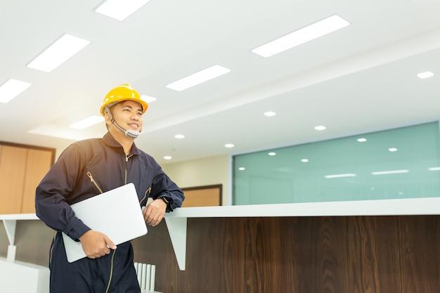 Un ingénieur industriel portant un casque de sécurité utilise un ordinateur portable à écran tactile. Photo Premium