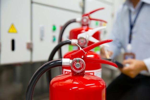 L'ingénieur Inspecte L'extincteur Dans La Salle De Contrôle Des Incendies. Photo Premium