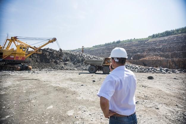 Un Ingénieur Des Mines En Chemise Blanche Et Casque Supervise Le Chargement Des Tombereaux Dans La Carrière Photo Premium