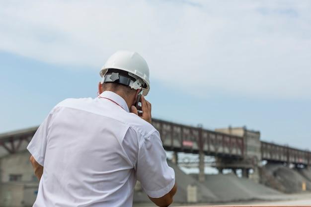 Un Ingénieur Des Mines En Chemise Blanche Et Casque Supervise Les Travaux D'un Atelier De Granit Photo Premium