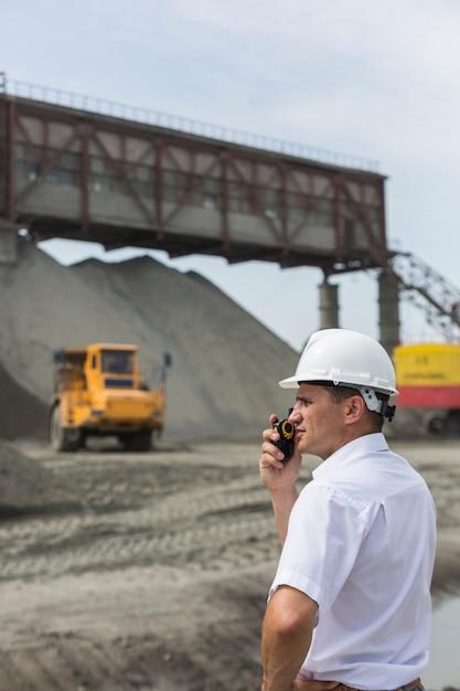 Un Ingénieur Des Mines Supervise Les Travaux D'un Atelier De Granit Tenant Un Talkie-walkie Photo Premium