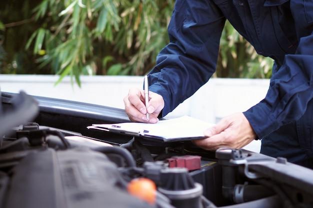 L'ingénieur moteur vérifie et répare la voiture. services de soins hors site Photo Premium