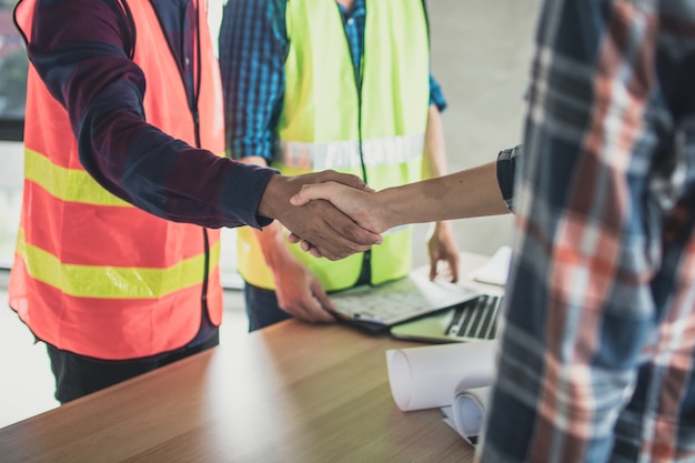 Ingénieur et ouvrier se serrent la main avant de planifier et de parler de la construction Photo Premium