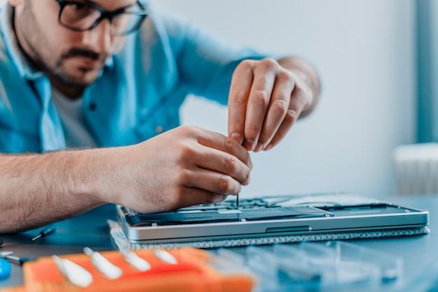 Un ingénieur répare un ordinateur portable avec un tournevis. Photo Premium