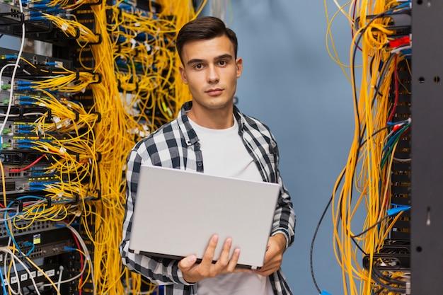 Ingénieur réseau sur la salle des serveurs plan moyen Photo gratuit