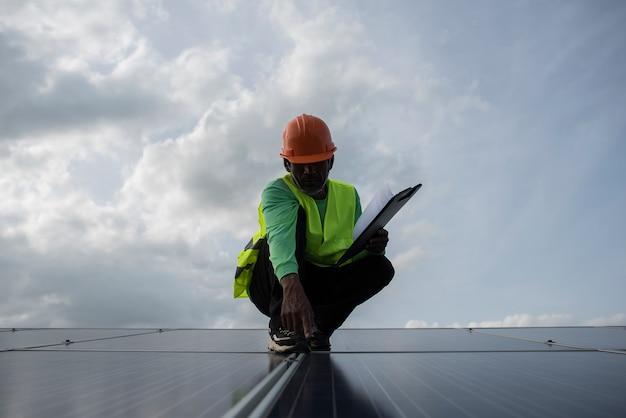 Un ingénieur technicien vérifie la maintenance des panneaux de cellules solaires. Photo gratuit