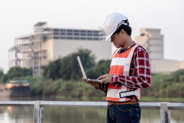 Ingénieur travaille sur des plans de chantier pour la construction d'immeubles de grande hauteur. concept de construction d'ingénieur. Photo Premium