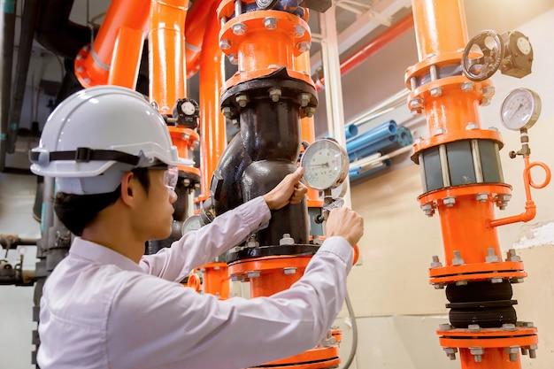 Ingénieur vérifiant la pompe à eau et le manomètre du condenseur. Photo Premium