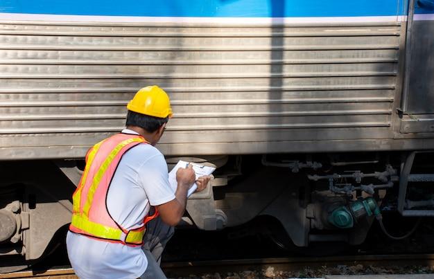 Ingénieur vérifiant le train pour l'entretien en gare Photo Premium