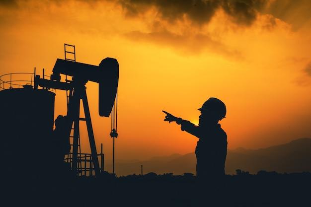 Ingénieurs et champs pétrolifères. exploration de forage pétrolier. silhouette. Photo Premium