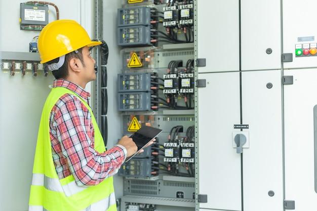 Les ingénieurs de maintenance asiatiques inspectent le système de protection de relais avec un ordinateur portable. bay cont Photo Premium
