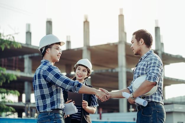 Les ingénieurs se serrent la main avec la secrétaire sur le côté. Photo Premium