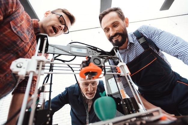 Les ingénieurs se tiennent autour de l'appareil et ils sont satisfaits du résultat Photo Premium