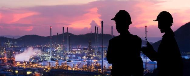 Les ingénieurs de silhouette sont des commandes permanentes l'industrie du raffinage du pétrole Photo Premium