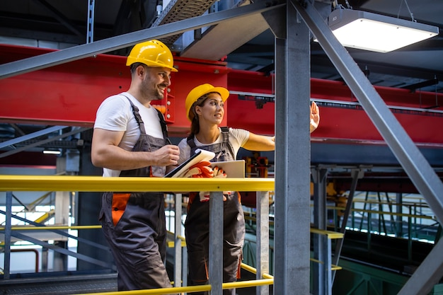Ingénieurs D'usine En équipement De Protection Debout Dans Le Hall De Production Et Partageant Des Idées Photo gratuit