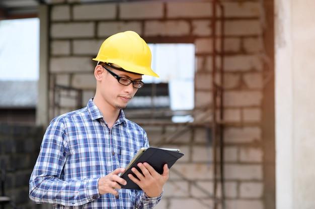 Les Ingénieurs Utilisent Des Tablettes Pour Vérifier La Construction. Ingénieur Portant Des Lunettes En Regardant La Tablette. Photo Premium
