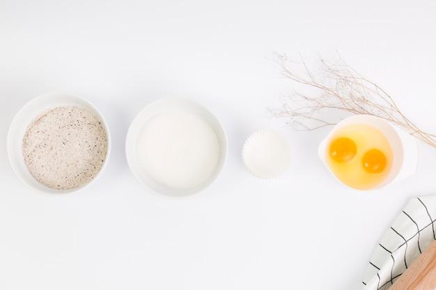 Ingrédient de cuisson cru disposé en rangée sur une surface blanche Photo gratuit