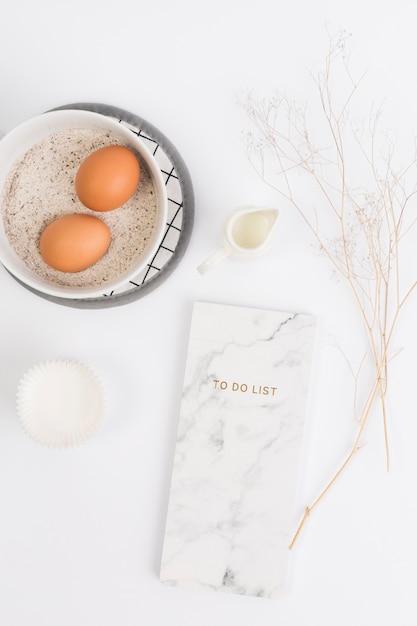 Ingrédient de cuisson sain avec le bloc-notes contre une surface blanche Photo gratuit