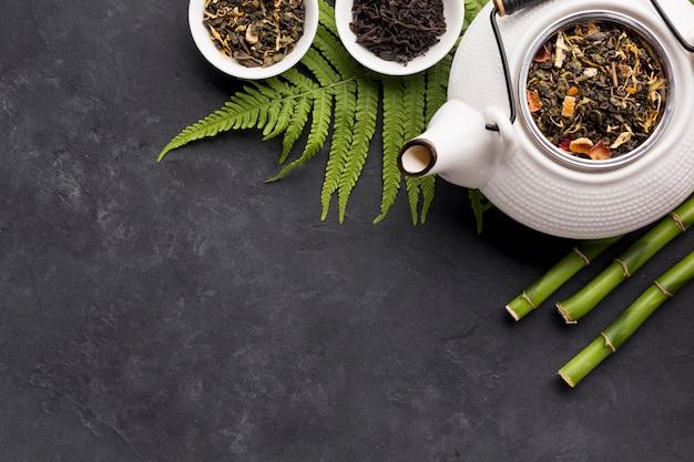 Ingrédient de thé séché et bâton de bambou avec des feuilles de fougère sur une surface noire Photo gratuit