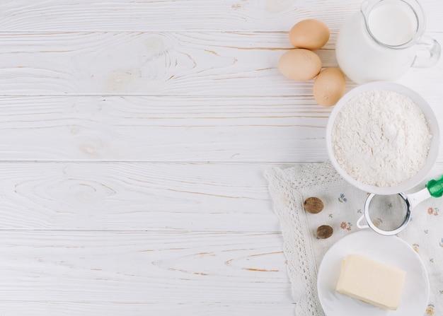 Ingrédients alimentaires sains et des outils sur une table en bois blanche Photo gratuit