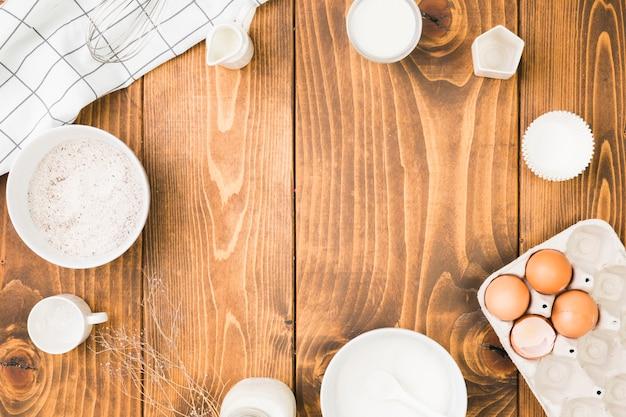 Ingrédients de cuisson frais organiser dans un cadre circulaire sur une table en bois Photo gratuit
