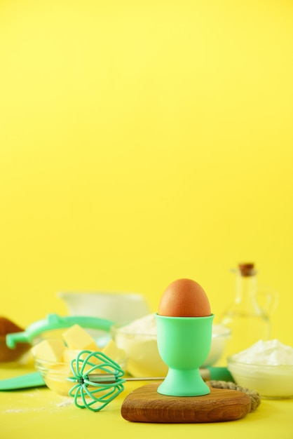 Ingrédients de cuisson sains - beurre, sucre, farine, œufs, huile, cuillère, pinceau, fouet, lait sur fond jaune. Photo Premium